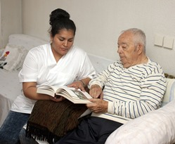 Nurse reading with Knik Fairview Alaska nursing home patient